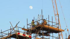 Workers at top of falsework, low angle telephoto shot, evening time Stock Footage