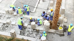 Group of workers remove decorative pavement tiles, area under reconstruction Stock Footage