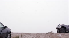 Two motorcycles jumping over hill between two SUVs in the falling snow. - stock footage