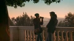 A girl takes pictures of her boyfriend, terrace in a public park at sunset Stock Footage
