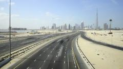 Wide highway at deserted area, modern Dubai Downtown skyline on horizon Stock Footage