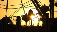Small Ferris Wheel cradle move over sun beam, silhouette view Stock Footage