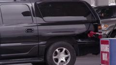 Black SUV fueling as minivan pulls in. - stock footage