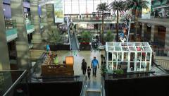 Modern Arabic mall interior, people move down on escalator, open atrium view Stock Footage