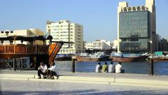 Two men sit on curb, rest on Dubai Creek embankment, talking Stock Footage
