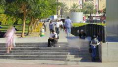 Unidentified pedestrians pass along pavement, Indian men sit on staircase Stock Footage