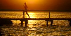 Young woman runs along pier / walkway over sea / water at sunset / sunrise Stock Footage