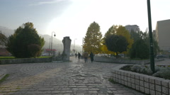 People walking by Duro Dakovic sculpture seen on a sunny day in Sarajevo Stock Footage