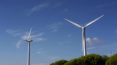Windmill electricity generator spins in wind, bright blue sunny day Stock Footage