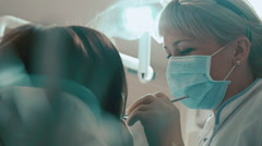 Dentist treats teeth of a young smiling girl Stock Footage