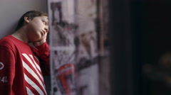 bored and annoyed child leaned on window sill, waiting for someone to play with - stock footage