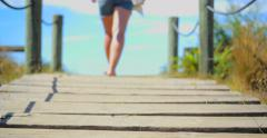 Young woman in flip flops walks over sandy wooden walkway to beach Stock Footage