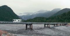 Campervan drives along bridge travelling through New Zealand Stock Footage