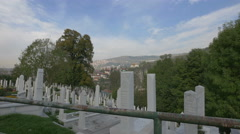 White tombstones and green trees in Groblje Alifakovac cemetery in Sarajevo Stock Footage