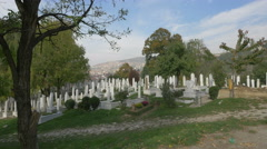 White tombstones, willow and other trees in Groblje Alifakovac in Sarajevo Stock Footage
