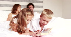 Stock Video Footage of Siblings reading book on bed