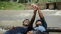 Happy Indian friends taking crazy selfie in river Stock Footage