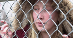 Young girl looking through fence with sadness in eyes 4k Stock Footage