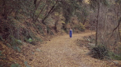 Young woman lost in a wood walking on leaves, naked feet Stock Footage