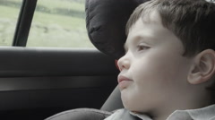 Closeup shot of a little boy travelling in a car with a booster seat Stock Footage