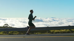 Young Man Running on Mountain Road at Sunset Above the Clouds. Slow Motion HD Stock Footage