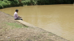 Indian fisherman sitting by the river - stock footage