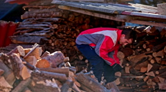 Person under shed roof putting together firewood Stock Footage