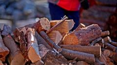 Picking firewood from top of pile outside close-up Stock Footage