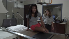 Nurse preparing x-ray of young woman's knee. Stock Footage