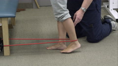 Tight shot of therapist working with woman for elastic band exercises. - stock footage
