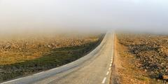 Stock Photo of Road through a barren plateau European route E69 fog midnight sun North Cape