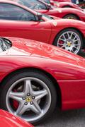 Row of red Ferrari on public display in a car show - stock photo