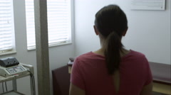 Woman and therapist in exam room preparing for back therapy. - stock footage