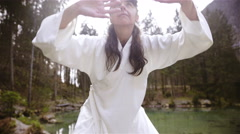 Woman in traditional clothes making Kung Fu forms at lake 4K Stock Footage