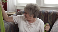 Tight shot of elderly woman doing exercise with elastic bands at home. - stock footage
