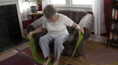 Elderly woman doing exercise with elastic bands at home. - stock footage