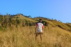 Marathon runner in 42.195 K.M. finisher t-shirt proudly standing on mountain. - stock photo