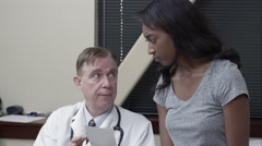 Doctor discussing prescription with young woman. - stock footage