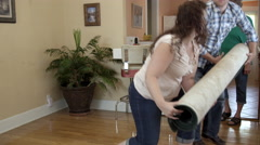 Stock Video Footage of Young man and woman carrying rolled up rug in elderly woman's home.