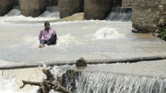 Indian guy sitting below dam Stock Footage