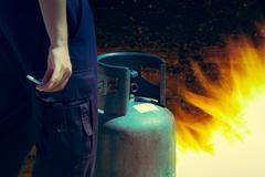 Cigarette in hand near gas tank cylinder can ignition of flammable, safety co Stock Photos