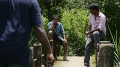 Group of indian buddies sitting on old bridge - stock footage