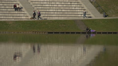 Walking and sitting on the lake shore in Bled Stock Footage