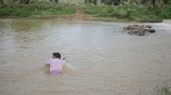 Indian man swimming in dirty lake Stock Footage