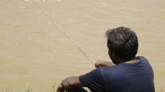 Stock Video Footage of Indian man sitting fishing at river