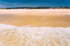 Sea Ocean Waves washing yellow sand at beach. Resort, holiday on Stock Photos