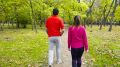 Man and woman in sportswear walking away from camera in the park slow motion Stock Footage