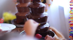 Enjoing chocolate fountain with fruits Stock Footage