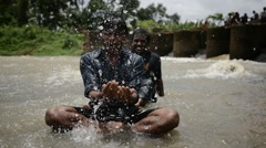 Indian man squirting water at dam - stock footage