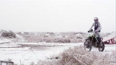 Man riding motorcycle in desert snow. Stock Footage